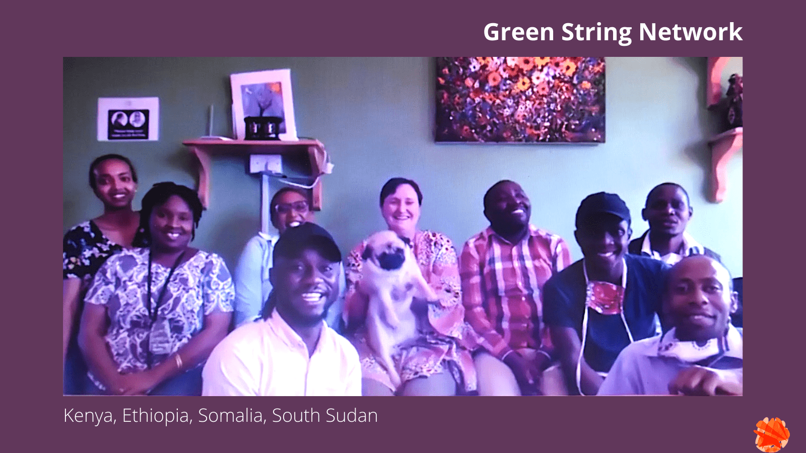 Portrait of the Green String Network team: Eigh people are sitting next to each other on a sofa, while two people crouch in front. Everyone is smiling at the camera. One woman holds a small dog in her lap. The walls behind them are a vibrant green, with paintings on them.