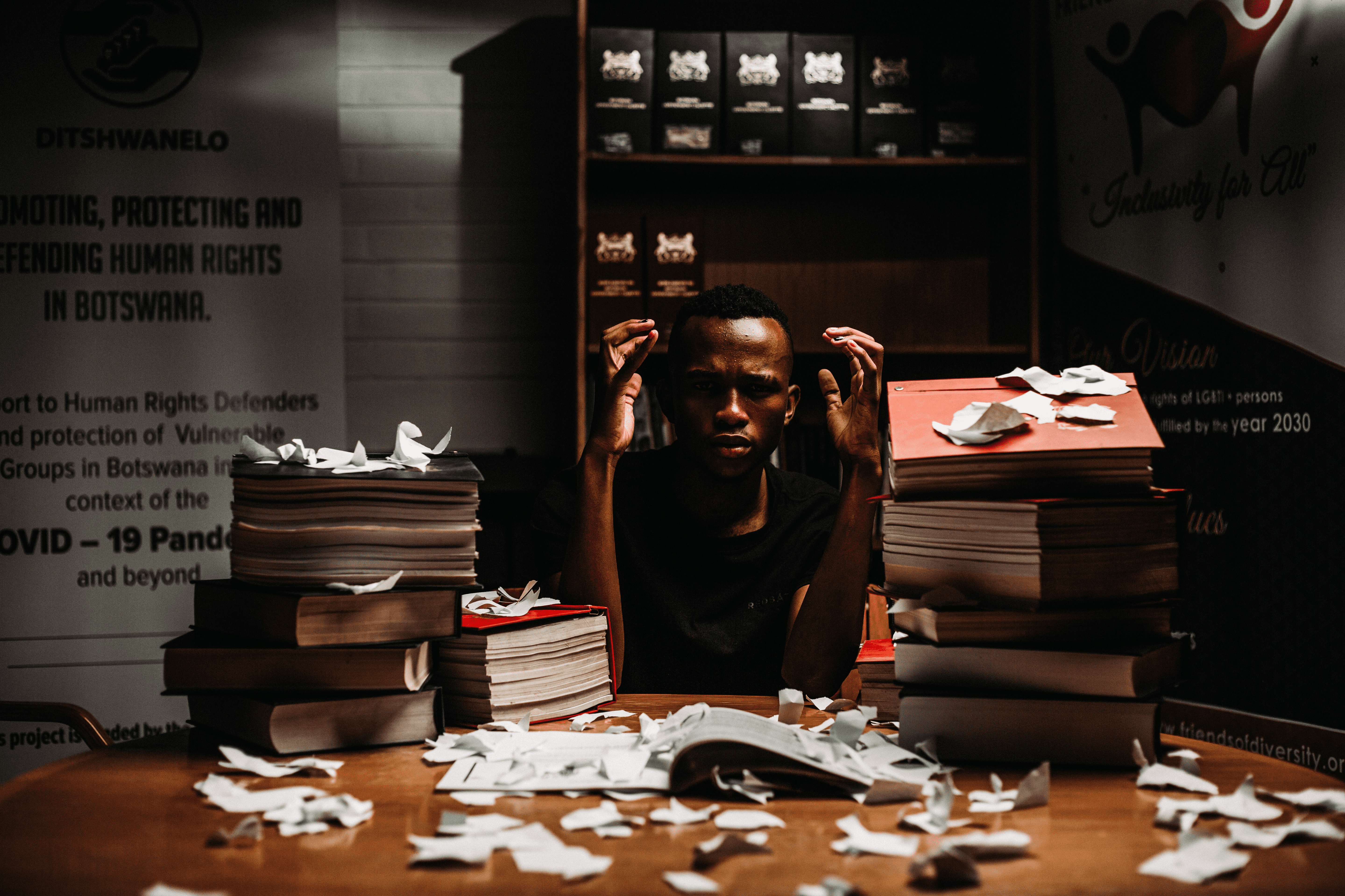 A person sitting on a table piled with files and pieces of torn paper