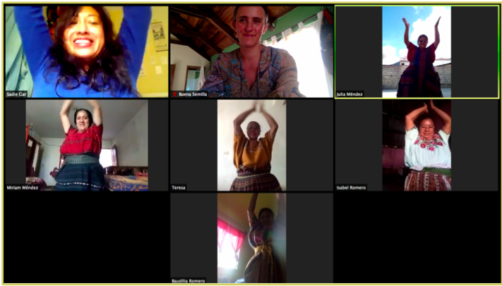 Screenshot of a zoom video call, with 8 people in their separate boxes, each holding their hands above their head and smiling.
