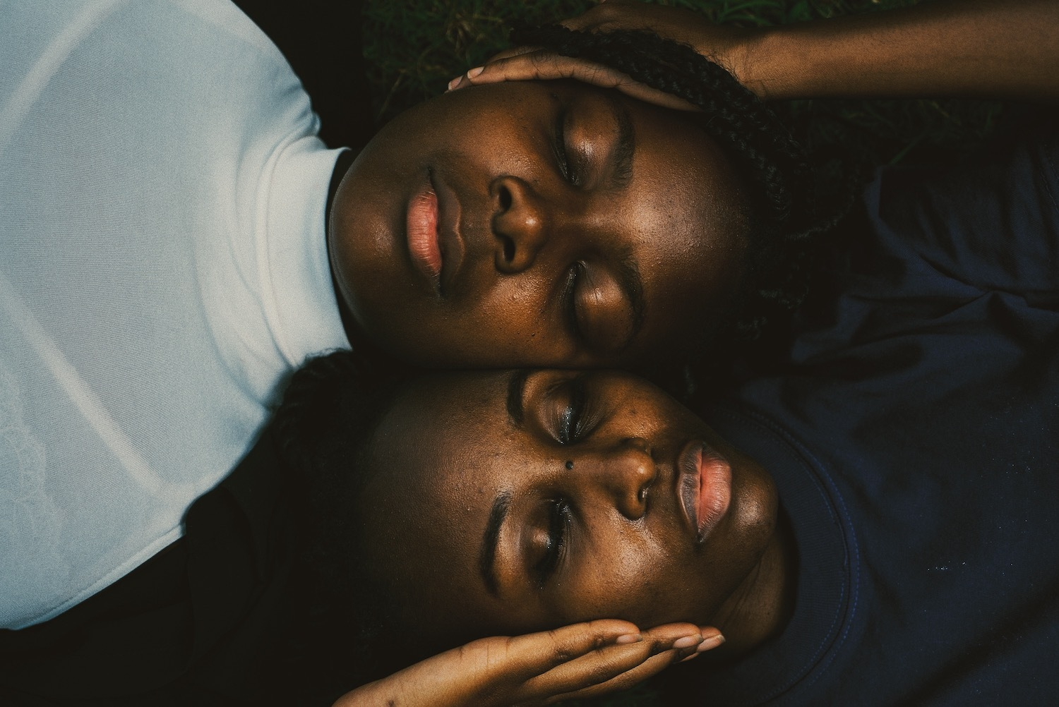 Two young women rest with their heads next to each other and eyes closed, with one hand on the other's cheek.