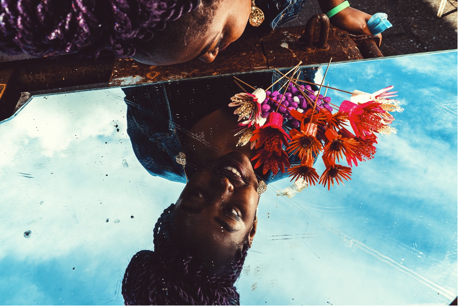 A young girl holding colourful flowers against the blue sky in background looking at her reflection in the mirror